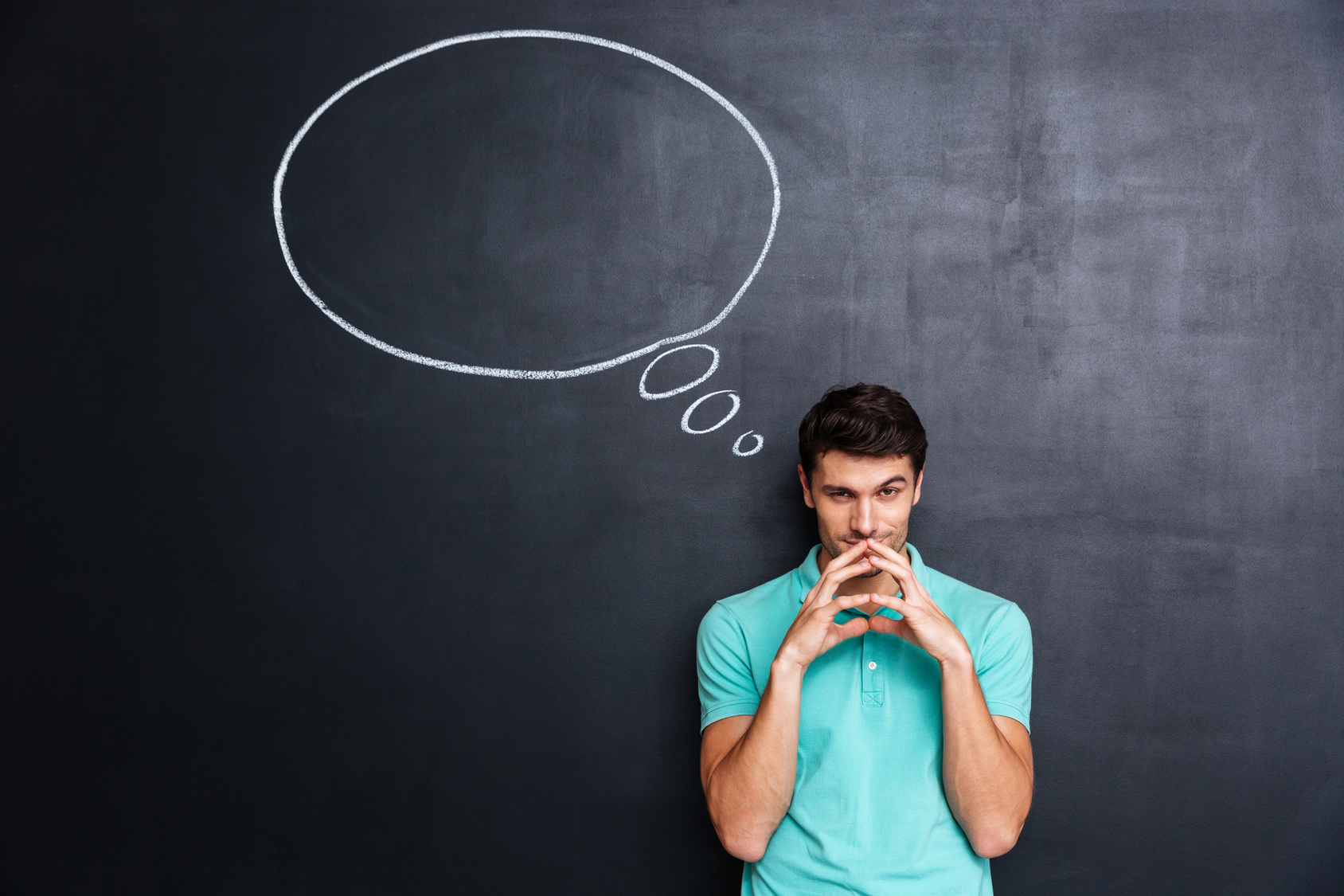 Smiling thoughtful young man over chalkboard background with blank speech bubble